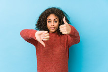 Young African American Curly Hair Woman Showing Thumbs Up And Thumbs Down, Difficult Choose Concept