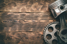 Old Car Engine Piston With Connecting Rod And Cog Wheel On Wooden Workbench Background With Copy Space. Machinery Abstract Background.