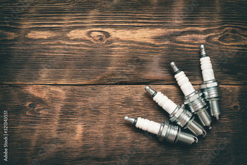 Leinwand Poster Spark plugs on brown wooden workbench background with copy space.