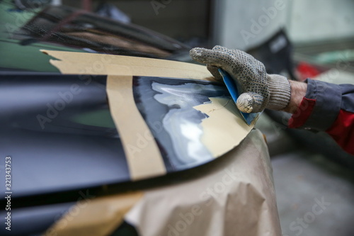 Fotomural local repairing car body with putty close up