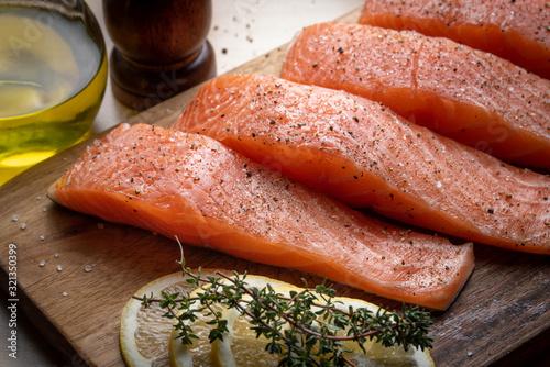 Photo seasoned salmon fillet on wooden cutting board