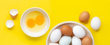 Fresh Eggs On Yellow Background.