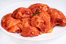 Chicken Legs In A Red Marinade On A White Plate. Top View. Chicken Meat Close-up.Dietary Meat. Cooking.Raw Marinated Chicken Legs For Grill And Bbq.Isolate.