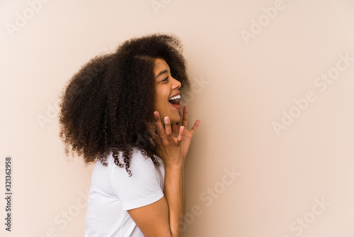 Young african american woman shouts loud, keeps eyes opened and hands tense Canvas Print