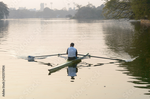 Photographie Individual Sports Speed Rower in Single scull crew rowing boat sliding racing shell on lake water oars in motion sitting sliding rigger seat doing exercise, fitness workout in sunset