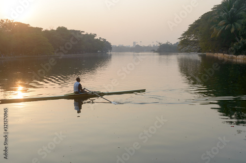 Individual Sports Speed Rower in Single scull crew rowing boat sliding racing shell on lake water oars in motion sitting sliding rigger seat doing exercise, fitness workout in sunset Tableau sur Toile