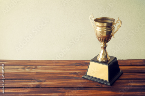 champion golden trophy on wood table with copy space ready for your design Fototapet
