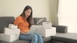 Asian woman using electronic devices on couch next to piles of boxes, cheering