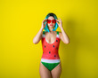 Portrait of a woman in a swimsuit with a picture of a watermelon. Stylish girl in a colored short wig posing in the studio on a yellow background.