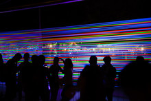 Silhouette Crowd Of People Standing Outdoor In Front Of Installation From Tensioned Neon Glowing Wires At Night. Concept Of Modern Exhibitions And Technology Development