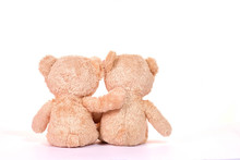 Two Teddy Bears Sitting On Whi...