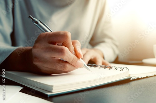 Asian woman is sitting and writing message in personal journal or diary as for remind vent some secret feeling, don't want anyone to know Wallpaper Mural