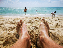 Feet Of A Man In The Sand On T...