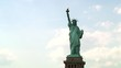 The majestic Statue of Liberty holding her torch and tabula ansata with white clouds as background. Tracking low angle. Full shot.