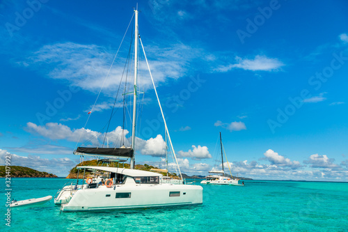 Fotografiet Turquoise colored sea with ancored catamarans, Tobago Cays, Saint Vincent and th