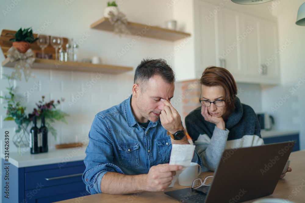 Fototapeta Young stressed Caucasian couple facing financials troubles, sitting at kitchen table with bills, checks and laptop computer and reading document from bank, looking frustrated and unhappy