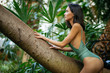 perfect sexual and slender woman in green bikini enjoy spending time among tropical plants, posing. beauty, fashion, spa, healthcare. summer vacation in exotic forest or botanic garden