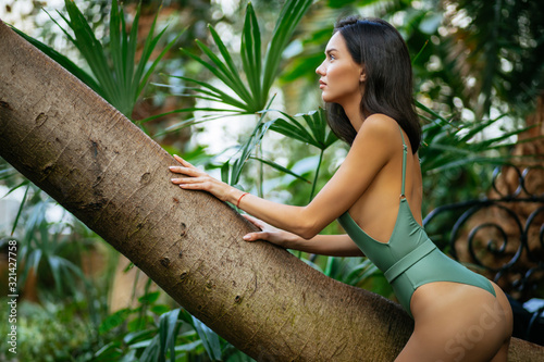 perfect sexual and slender woman in green bikini enjoy spending time among tropical plants, posing Wallpaper Mural