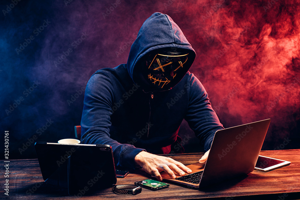 Fototapeta hacker man typing on laptop, hacking computer system. male in mask and pullover. unrecognizable incognito male sit in hood and try to breach the security of laptop system. neon smoke in background