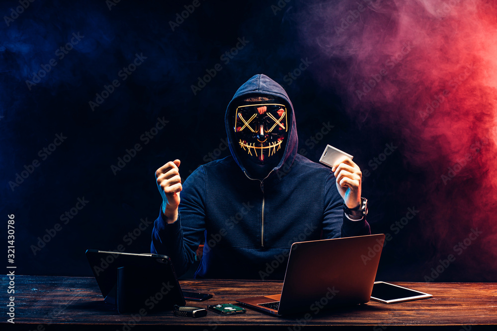Fototapeta anonymous hacker in mask after successful getting access to bank card, raised hands up, hold bank card in one hand, going to withdraw money from it. isolated over black background