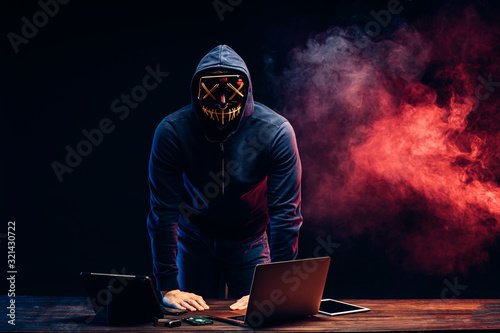 Fototapety, obrazy: young programmer in a smoke-filled background, a hacker in mask, trying to hack into a computer system, unrecognizable male stand above table with laptop