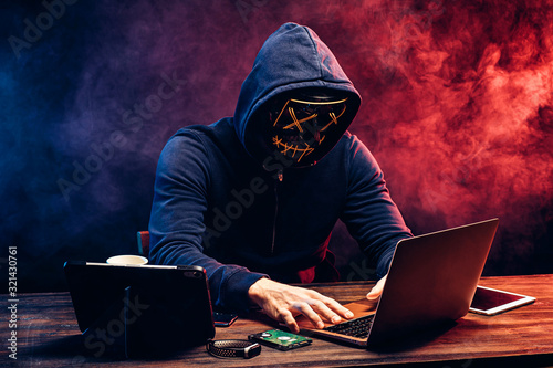 hacker man typing on laptop, hacking computer system. male in mask and pullover. unrecognizable incognito male sit in hood and try to breach the security of laptop system. neon smoke in background
