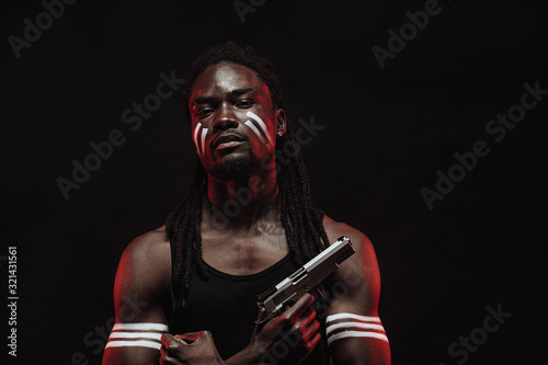 young serious african man in black shirt isolated over black background, dangerous man hold gun in hands ready to kill the enemy, red neon rays falling on his face Wallpaper Mural