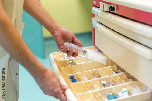 Chariot d'urgence médical produits injectables office infirmier prendre seringue Billede på lærred