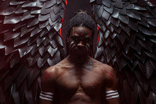 Tormented African Angel With Black Wings, Angel Has Strong Muscular Body And Dreadlocks On Head. Serious Male In The Flesh Of Angel Stand Suffering Isolated Over Dark Space. Fantasy, Fiction Concept