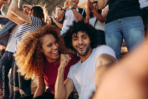 Fototapeta Couple of spectators taking selfie in stadium obraz