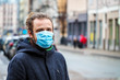 Handsome young European man in winter clothes on the street with a medical face mask on. Closeup of a 35-year-old male in a respirator to protect against infection with influenza virus or coronavirus