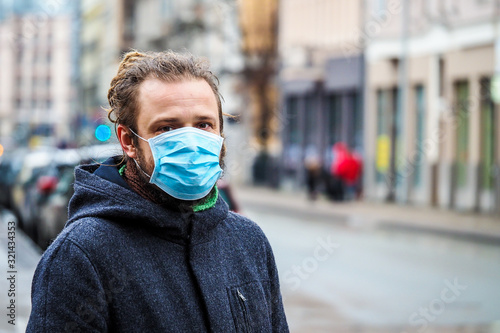 obraz dibond Handsome young European man in winter clothes on the street with a medical face mask on. Closeup of a 35-year-old male in a respirator to protect against infection with influenza virus or coronavirus