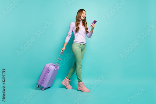 fototapeta na ścianę Full length photo of cheerful lady walking airport registration with rolling suitcase browsing telephone wear lilac sweater green pants shoes isolated pastel teal color background
