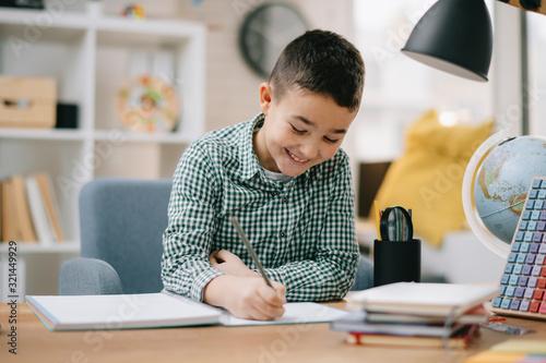 Cute little boy doing homework. Child learning foe school.