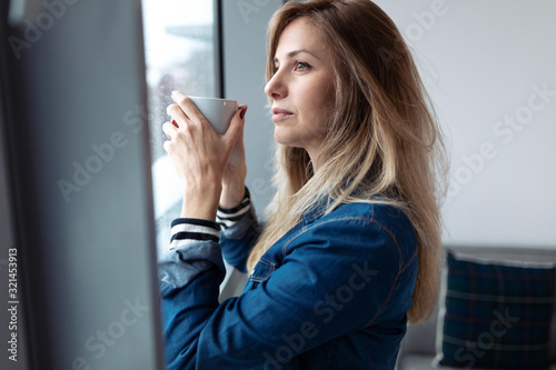Pretty young woman looking through the window while drinking coffee in the living room at home.