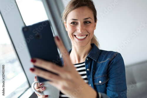 Fototapeta Pretty young woman taking a selfie while drinking coffee near to the window in the living room at home. obraz