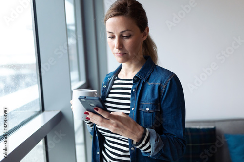 Pretty young woman using her mobile phone while drinking coffee near to the window in the living room at home.