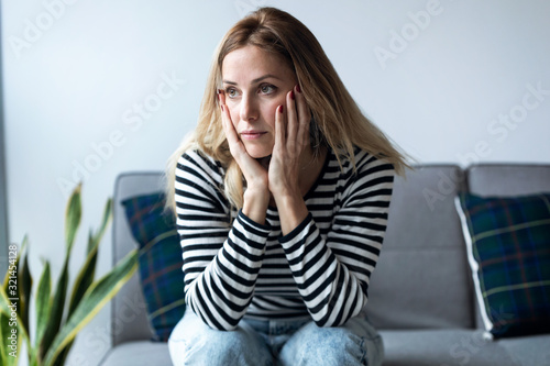 Obraz Depressed young woman thinking about her problems while sitting on the sofa at home. - fototapety do salonu