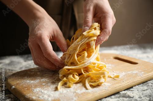 Woman preparing pasta at table, closeup view Fotobehang