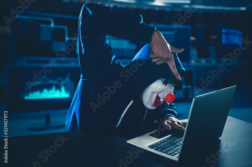 Fotomural Hacker wearing clown mask using a laptop