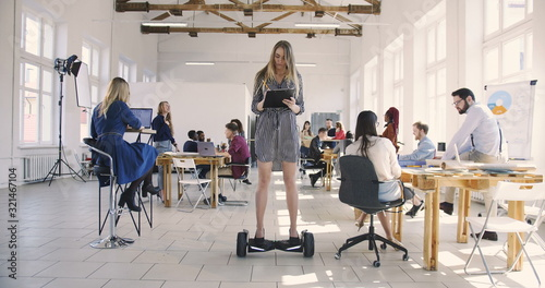 Fotografía Young confident serious blonde business woman in dress riding electric gyroscooter in modern loft multiethnic office
