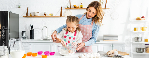 Fototapeta Beautiful attractive mother standing behind cute daughter while kneading dough, panoramic shot obraz