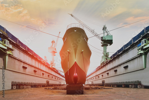 Cargo ship moored in floating dry dock under repair and maintenance in Shipyard industry ship building big ship repair with sunset background Tapéta, Fotótapéta