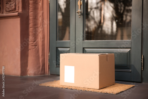Delivered parcel on door mat near entrance - 321471788