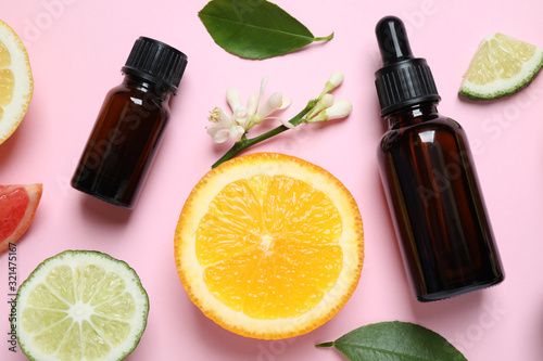 Fototapeta Flat lay composition with bottles of citrus essential oil on pink background obraz
