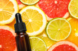 canvas print picture Bottle of essential oil on pile of citrus slices, flat lay. Space for text