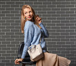 canvas print picture Young woman in warm sweater and with stylish bag on dark brick background