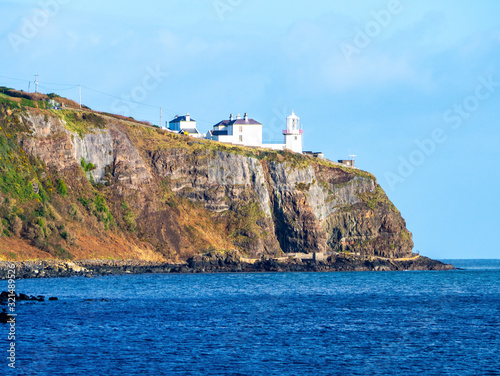 Blackhead Lighthouse in Whitehead village on a steep cliff on the Atlantic coast in County Antrim, Northern Ireland, UK
