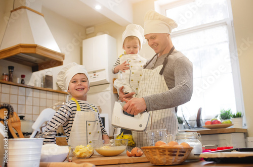 Photo Dad and his sons in chef's hats are cooking