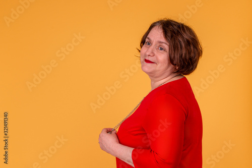 Half length portrait of   an elderly retro woman wearing  red dress against a ye Canvas-taulu